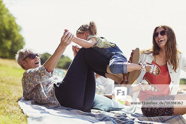 Verspielte Großmutter und Enkelin auf Decke im sonnigen Feld