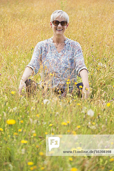 Portrait Seniorin im Schneidersitz im ländlichen Raum