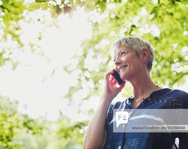 Lächelnde Seniorin beim Telefonieren unter Bäumen