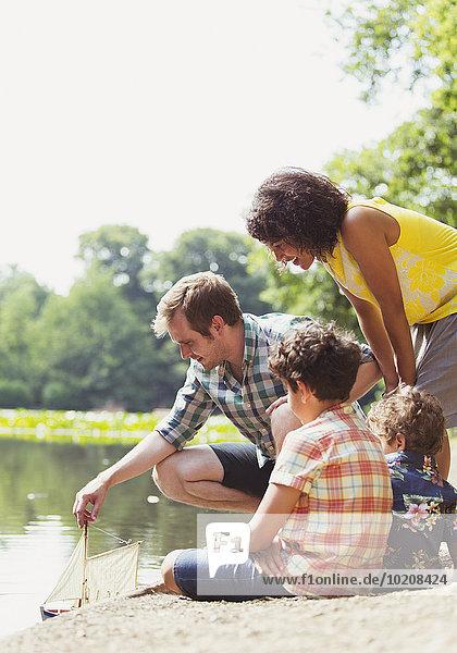 Familienspiel mit Spielzeug-Segelboot am Seeufer