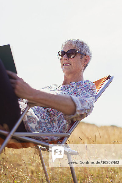 Seniorin liest Buch im sonnigen Feld