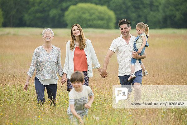 Mehrgenerationen-Familie beim Händchenhalten und Wandern im ländlichen Raum