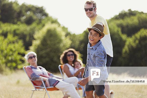 Portrait Verspielter Sohn zieht Vater in sonniges Feld