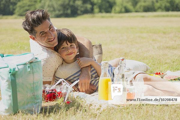 Portrait liebevoller Vater und Sohn entspannt auf Picknickdecke im sonnigen Feld