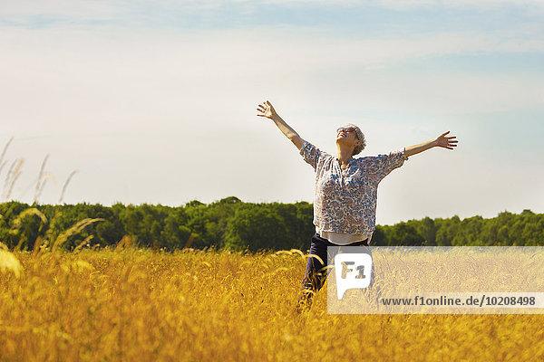 Überschwängliche Seniorin mit ausgestreckten Armen im sonnigen ländlichen Feld