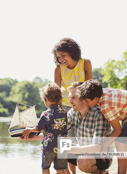 Familie mit Spielzeug-Segelboot am sonnigen Seeufer