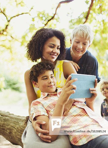 Mehrgenerationen-Familie mit digitalem Tablett im Außenbereich