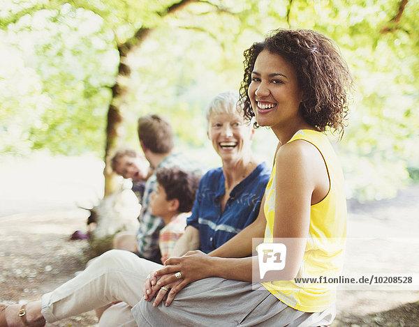 Portrait lachende Mehrgenerationen-Familie im Wald