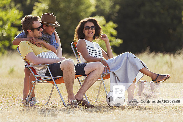 Lächelnde Familie entspannt im sonnigen Feld