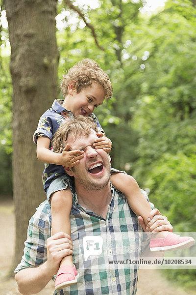 Verspielter Sohn  der Vaters Augen im Wald bedeckt.