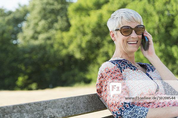 Lächelnde Seniorin am Handy im Park