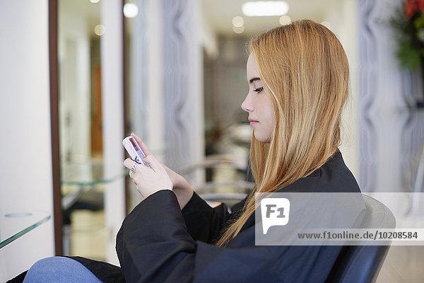 Frau SMS mit Handy im Friseursalon