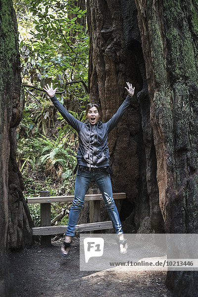 Caucasian woman jumping for joy in forest