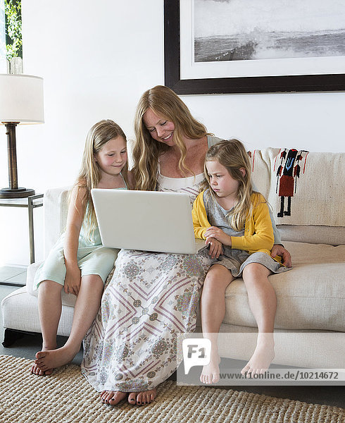 Caucasian mother and daughters using laptop on sofa