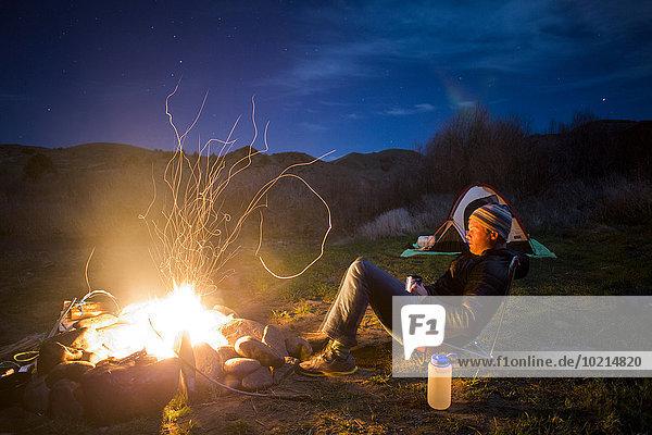 Lagerfeuer nahe Europäer Mann Vereinigte Staaten von Amerika USA Entspannung Feld