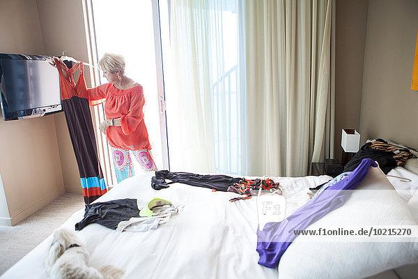 Older Caucasian woman choosing outfit in bedroom