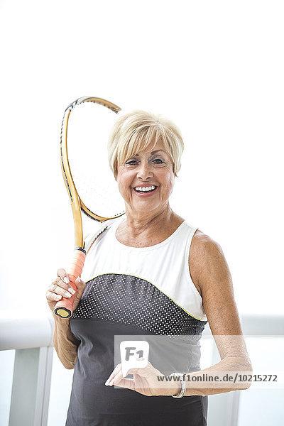 Older Caucasian woman holding tennis racket on balcony