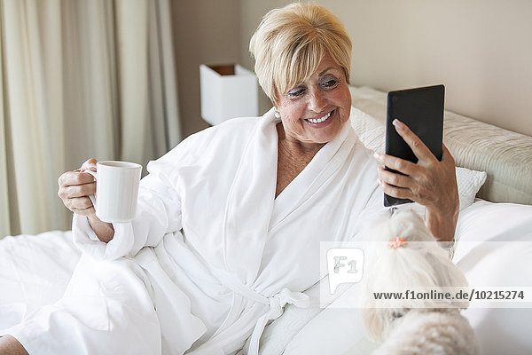 Older Caucasian woman and dog using digital tablet on bed