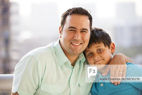 Hispanic father hugging son and smiling