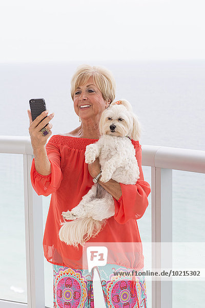 Older Caucasian woman taking selfie with dog on balcony