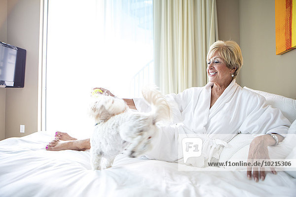 Older Caucasian woman petting dog on bed