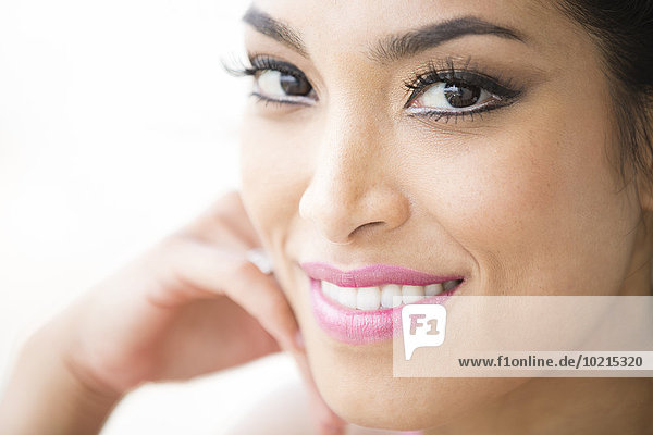 Close up of face of smiling Hispanic woman