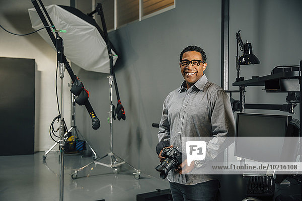 Mixed race photographer holding camera in studio