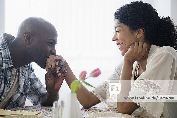 Mann Freundin küssen Restaurant Tisch