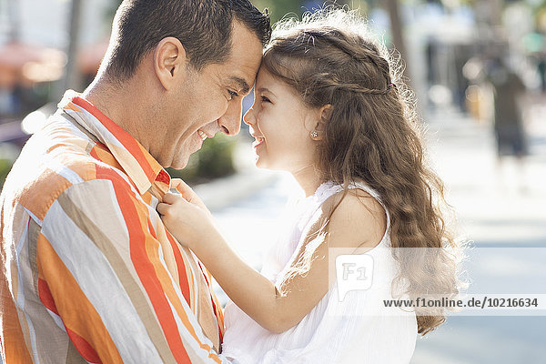 Close up of Hispanic father and daughter touching foreheads