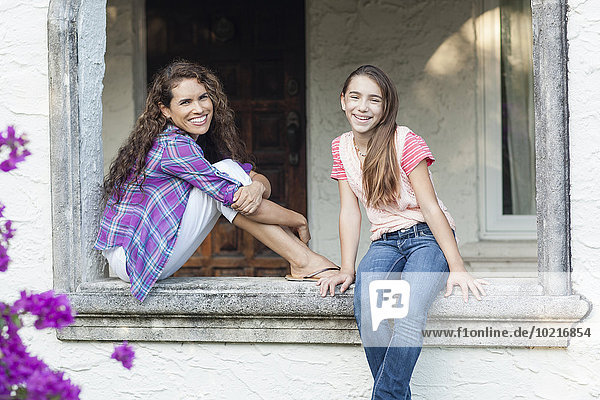 Hispanic mother and daughter sitting in window sill outdoors