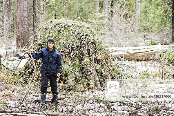 Hispanic boy building hut from branches in forest