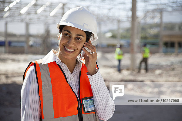 Architect talking on cell phone at construction site