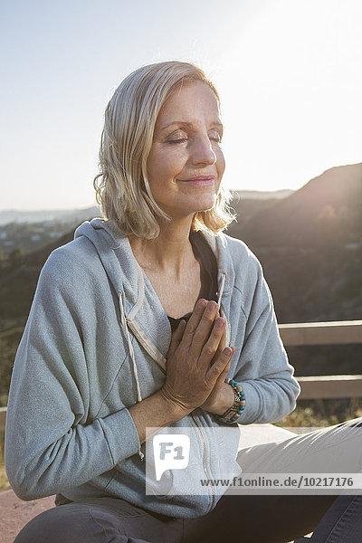 Caucasian woman meditating on hilltop