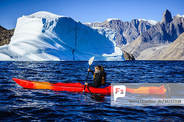 Woman paddling canoe near glaciers in remote river