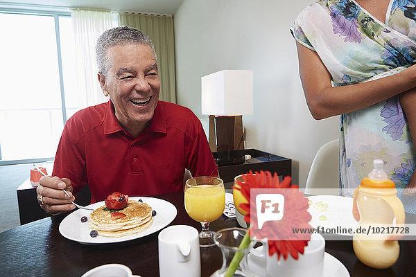 Menschlicher Vater Tochter essen essend isst Pfannkuchen Tisch