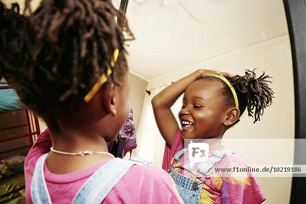 Black girl admiring herself in mirror
