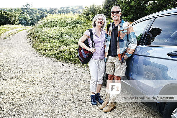 Caucasian couple smiling at car on hiking trail