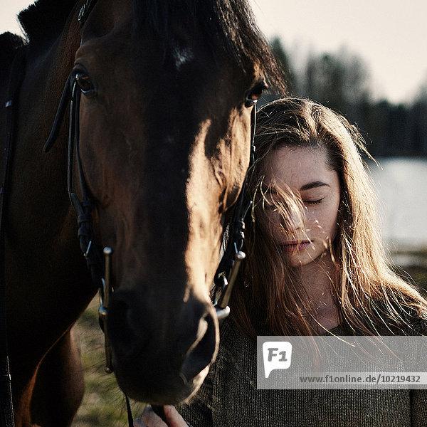 Caucasian woman walking with horse in field