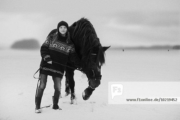 Caucasian teenage girl leading horse in snowy field