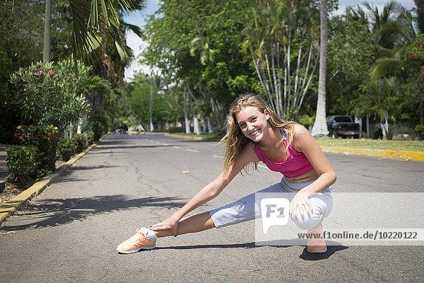Mexiko  Nayarit  Teenager-Mädchen beim Stretching auf der Straße