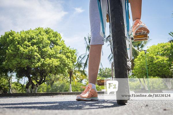Mexiko  Nayarit  Beine eines jungen Mädchens auf einem Fahrrad