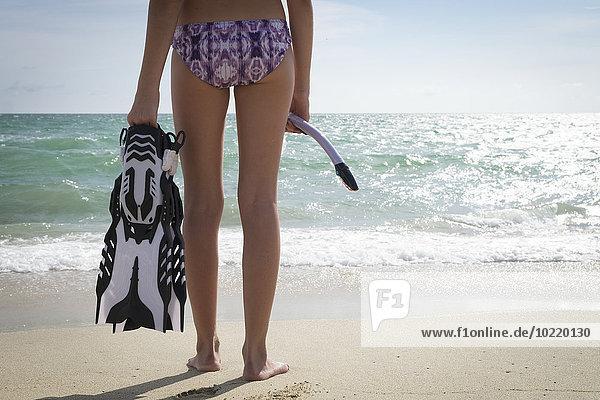 Mexiko  Nayarit  Teenagermädchen mit Schnorchel und Flossen vor dem Meer stehend