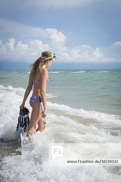 Mexiko  Nayarit  Teenagermädchen mit Schnorchel und Flossen beim Spaziergang ins Meer