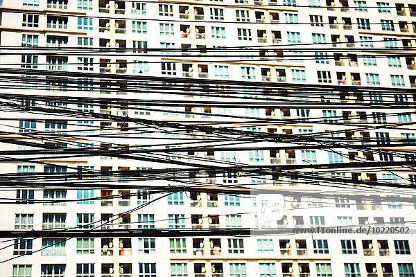 Thailand  Bangkok  verwickelte und unordentliche Elektrokabel vor einer Fassade