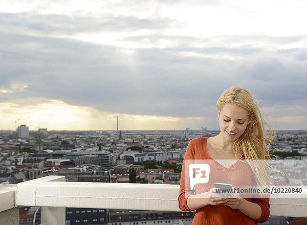 Deutschland  Berlin  junge Frau beim Blick auf ihr Smartphone