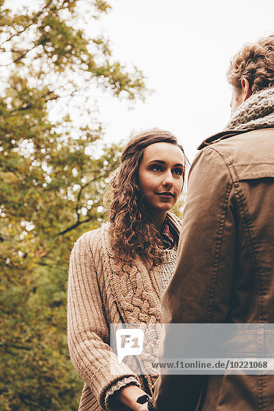 Young couple in love holding hands in an autumnal park
