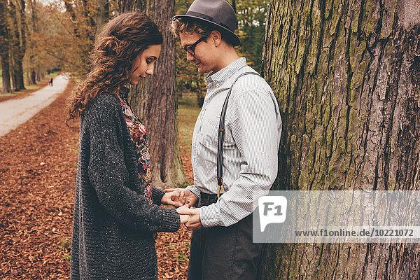 Verliebtes junges Paar hält sich an den Händen in einem herbstlichen Park.