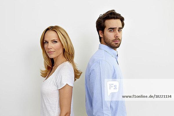Porträt eines Paares  das Rücken an Rücken vor weißem Hintergrund steht.