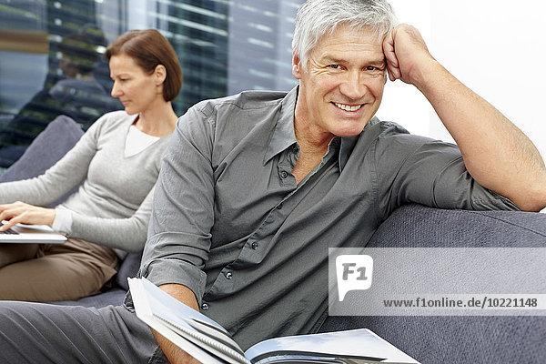 Porträt eines entspannten Mannes  der mit einem Buch auf der Couch sitzt  während seine Frau im Hintergrund den Laptop benutzt.