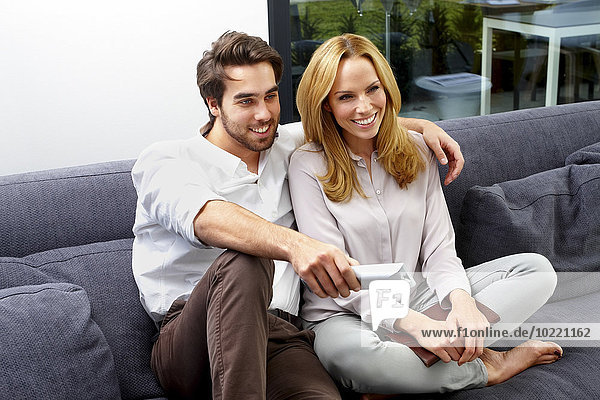 Happy couple sitting together on couch watching TV show